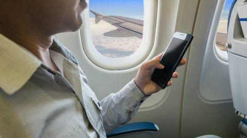 53383678 - man using smart phone in airplane.